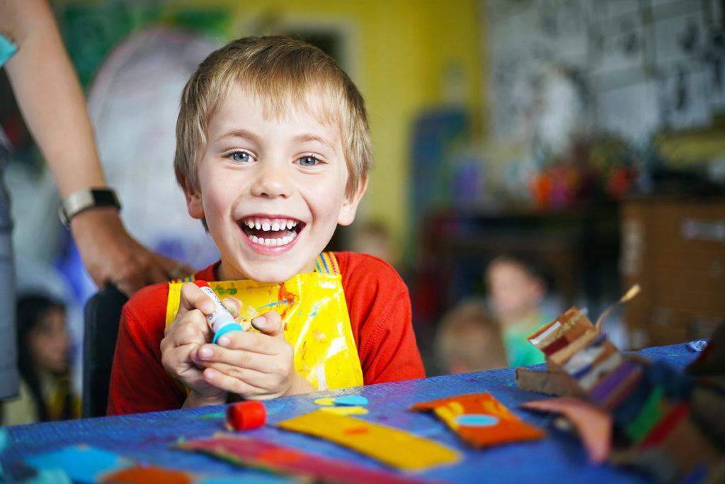Smiling boy with a glue stick