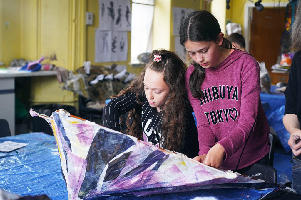 Two children making a tissue paper structure on a table