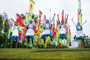 Hardeep and bhangra dancers jumping in front of colourful flags