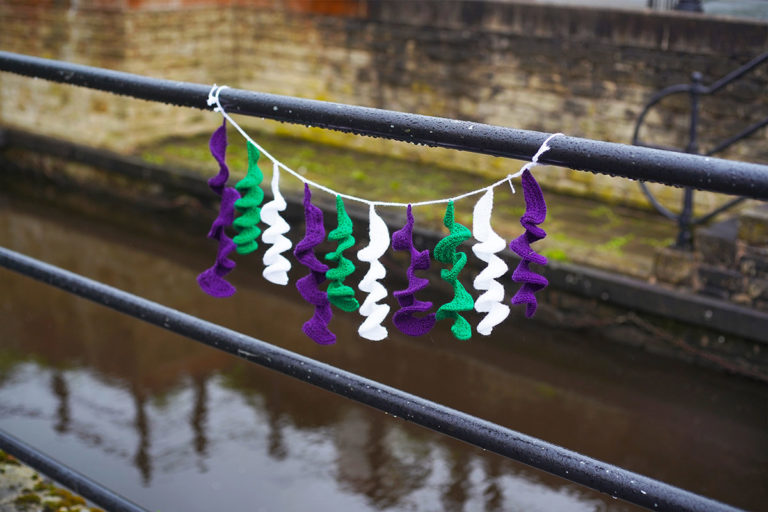 Purple, green and white knitted spirals hanging from a railing