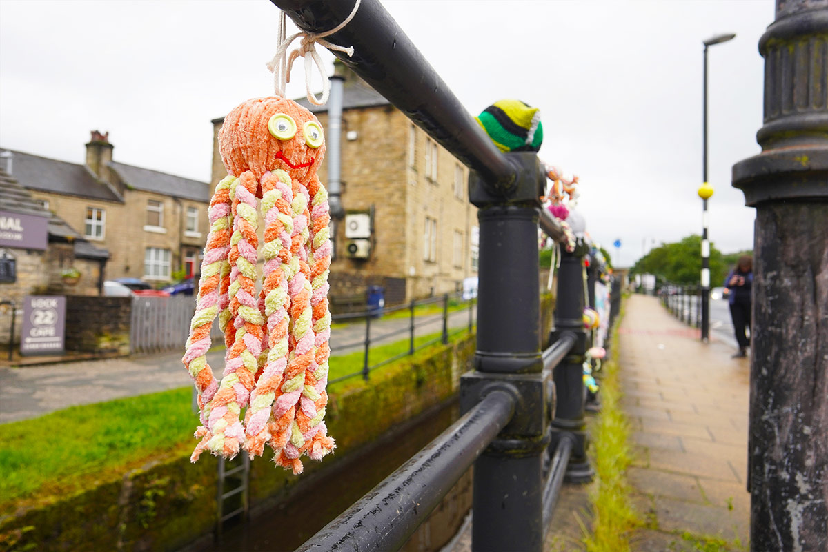 Knitted octopus hanging from railing