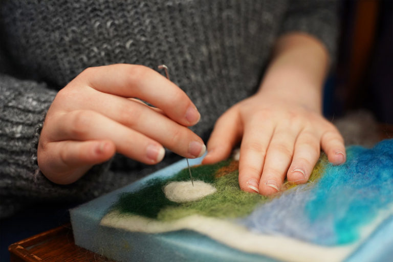 Close up of hands sewing into felt
