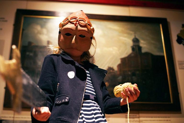 Child wearing a paper mache mask