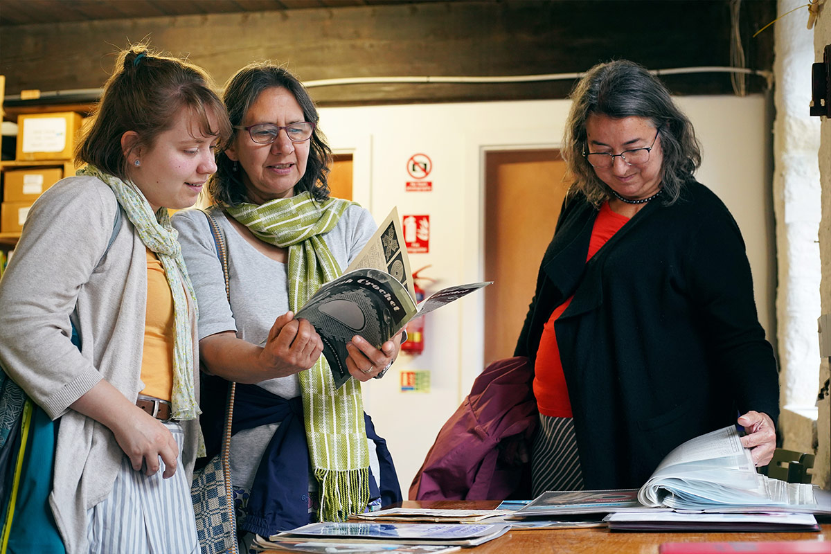 Three women looking at books on a table