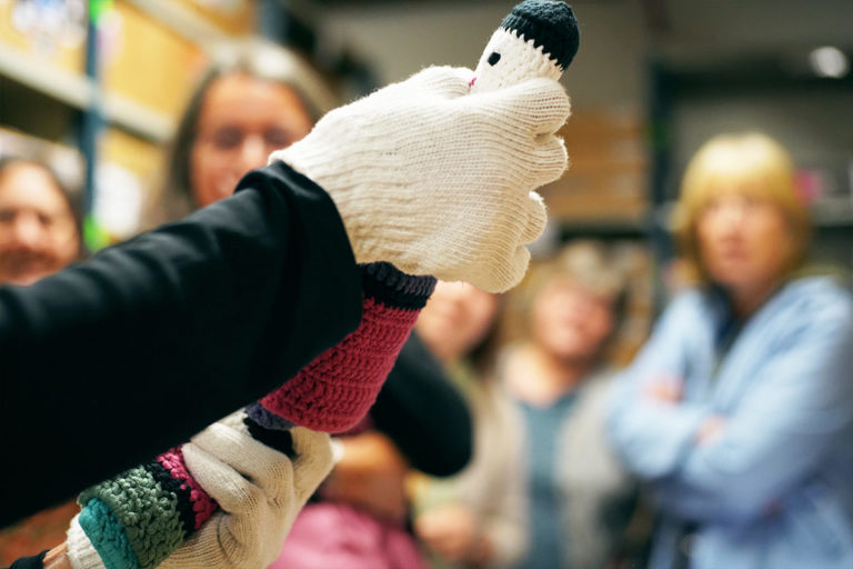 Gloved hand showing a crowd of people a knitted item