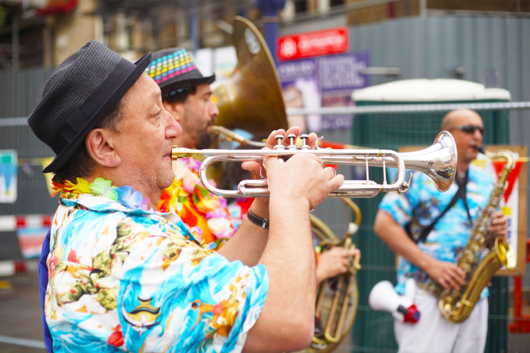 Brass instruments being played by men in flamboyant shirts