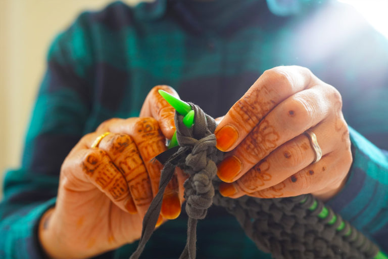 Woman with henna patterned hands knitting with t-shirt yarn
