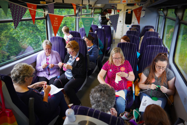 People knitting in a train carriage