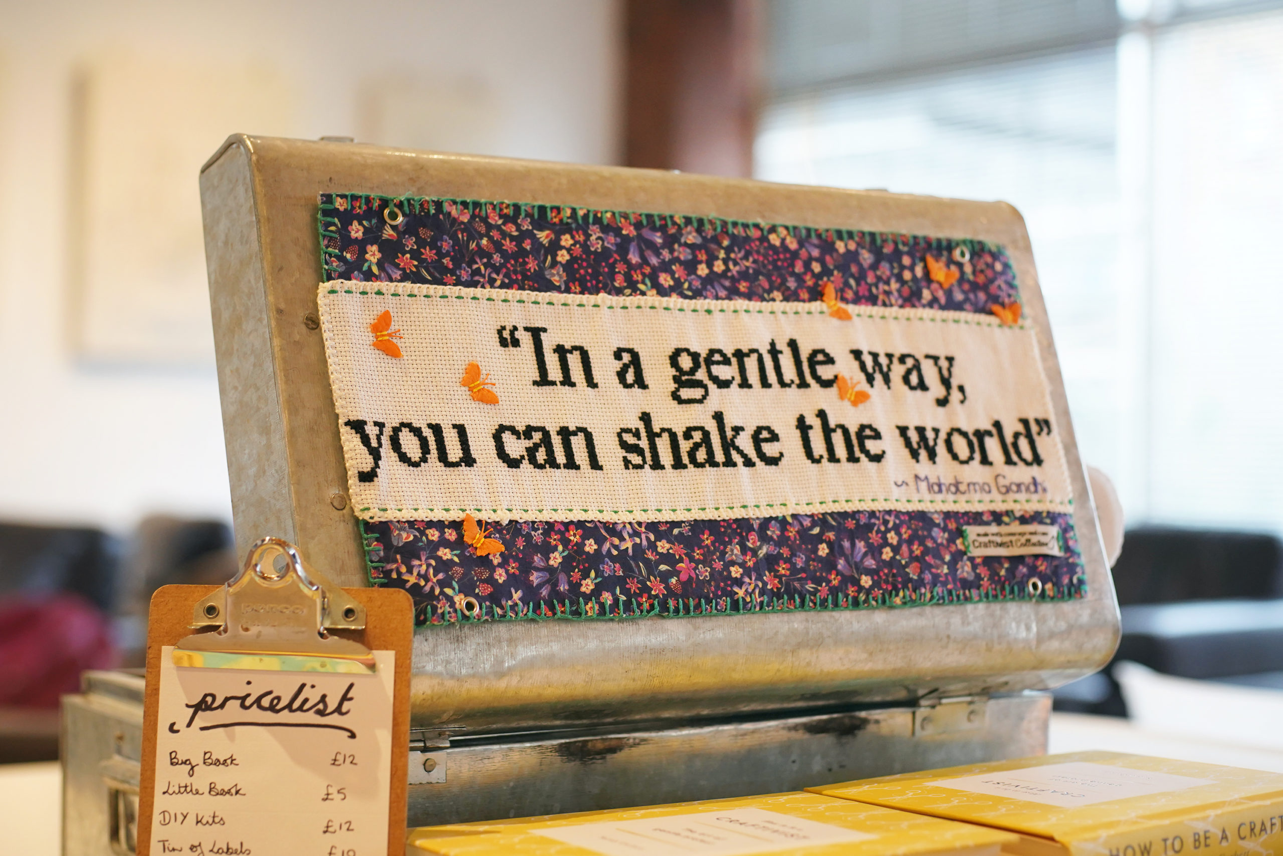 "Tin lid with embroidered panel that says ""In a gentle way you can shake the world"""