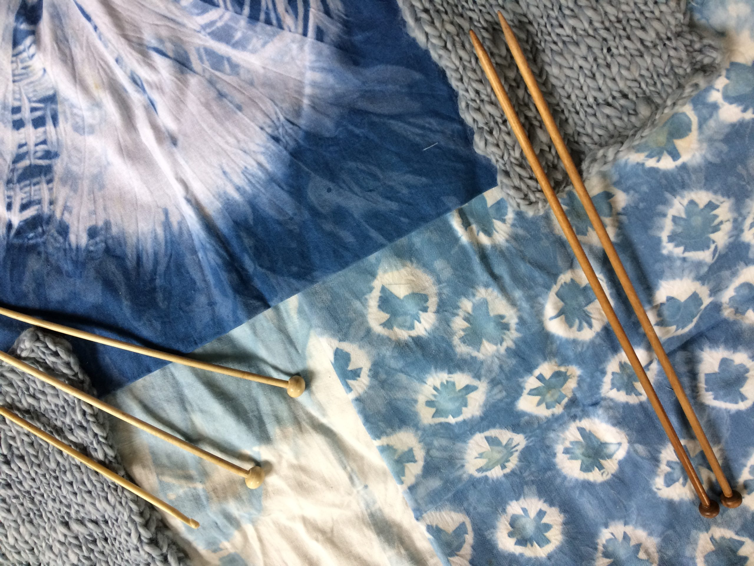 Naturally dyed fabric in blues with knitting needles