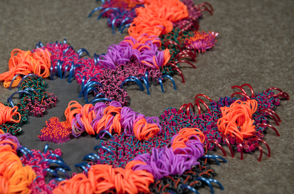 Brightly coloured raised embroidery in orange, pink, lilac, blue and green