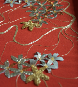 Close up of gold embroidery, including flowers and threads
