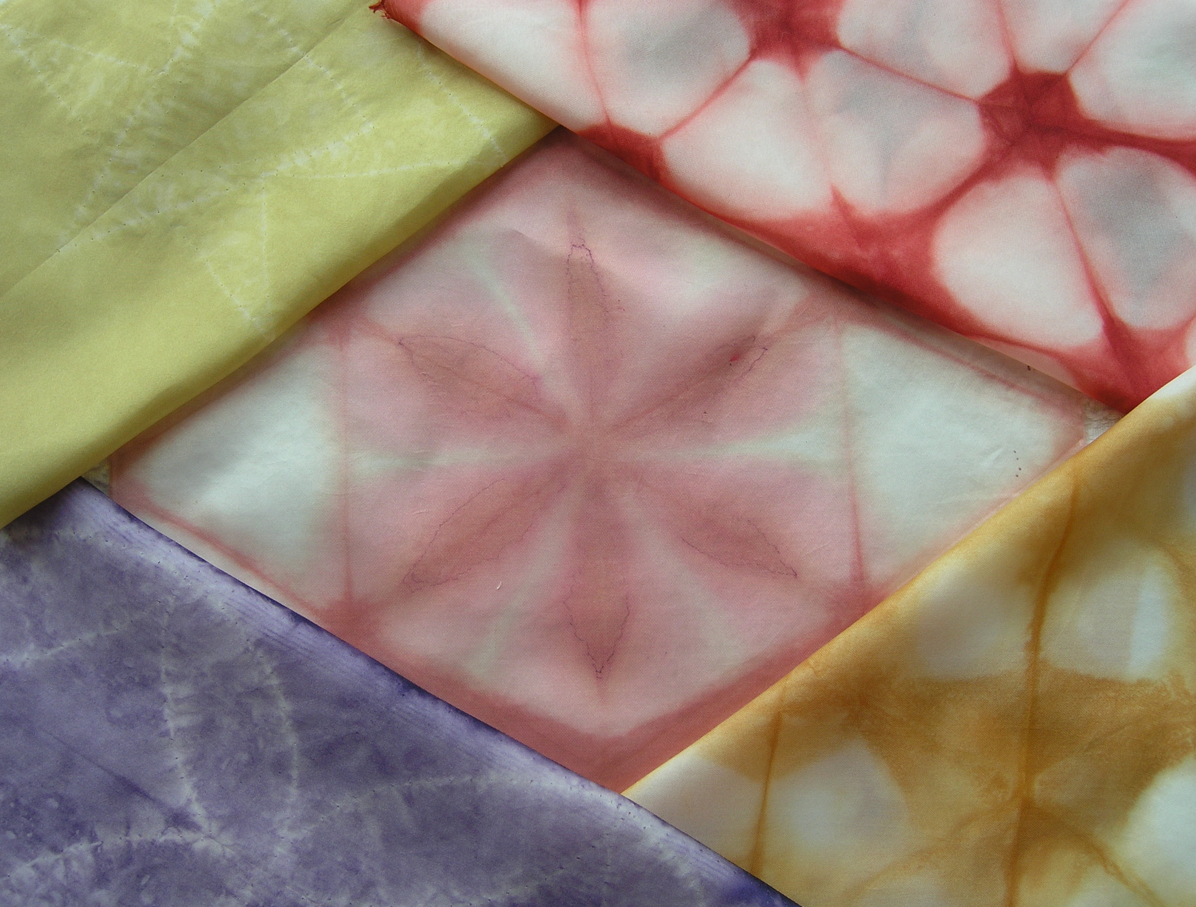 patches of tie dyed fabric in reds, yellows and blues