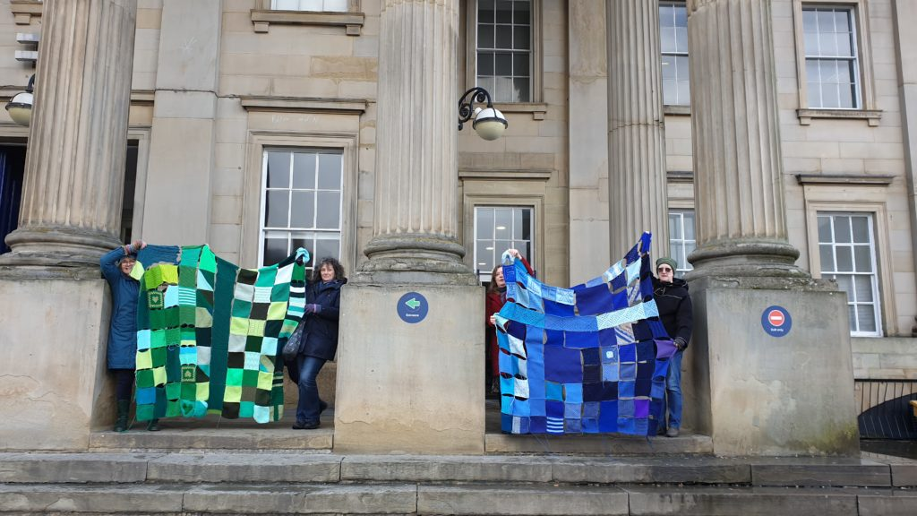 Four women next to the pillars at Huddersfield Train Station holding up two 'blankets' created from green and blue knitted squares