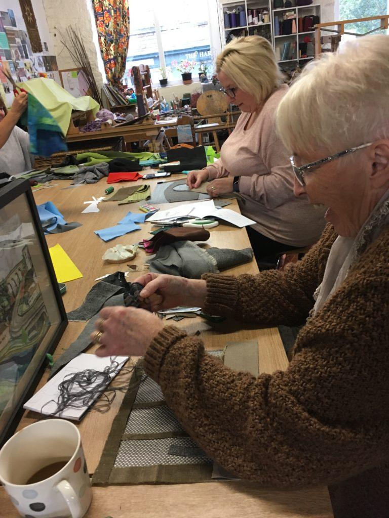 Older ladies taking part in a sewing workshop