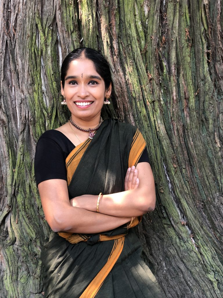 Photo of Dr Chamu Kuppuswamy wearing a sari and leaning against a tree