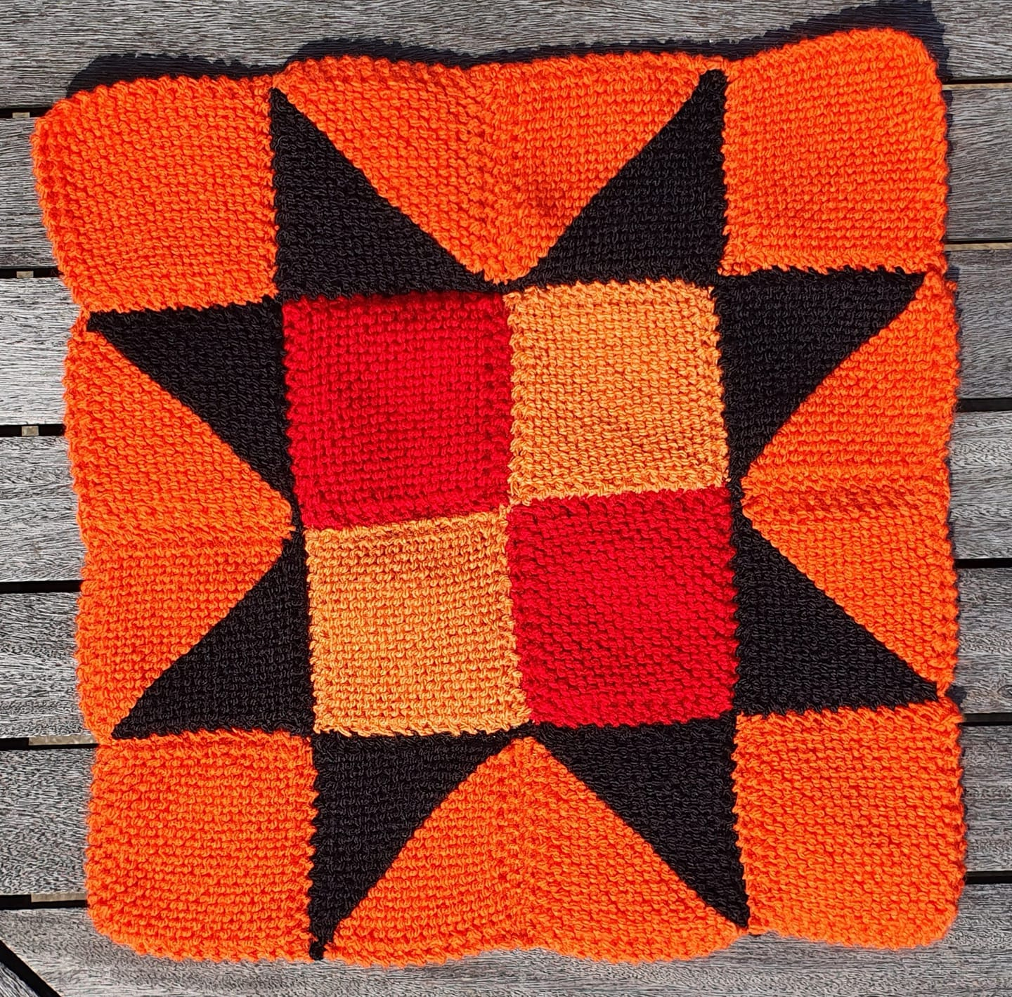 knitted square with geometric orange and black pattern