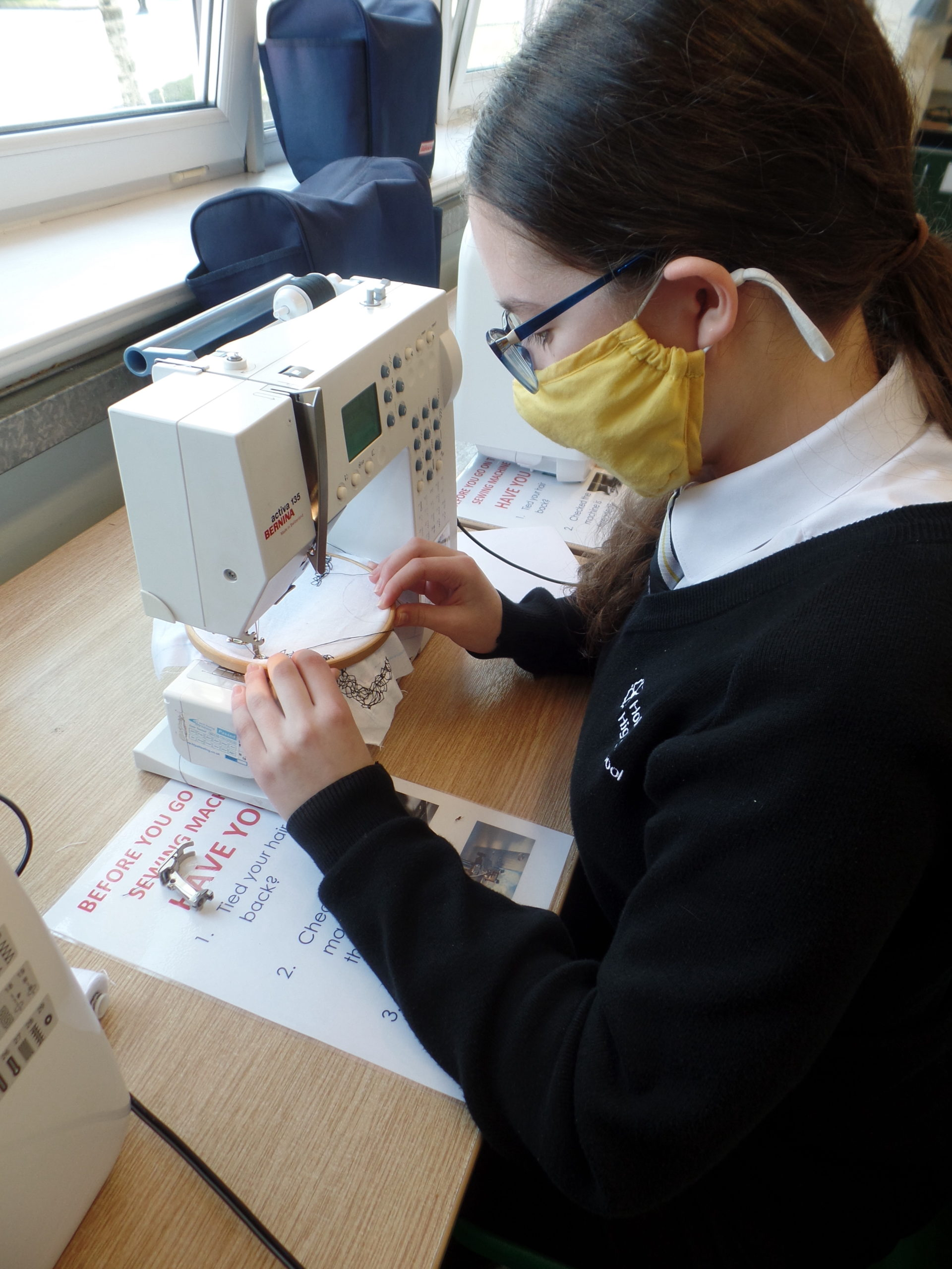 school girl with white skin and dark hair using a sewing machine