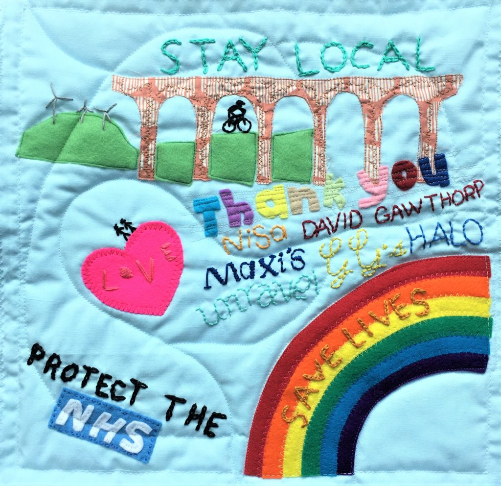 quilted textile art depicting a rainbow, heart, protect the NHS lettering and a viaduct on a pale blue background