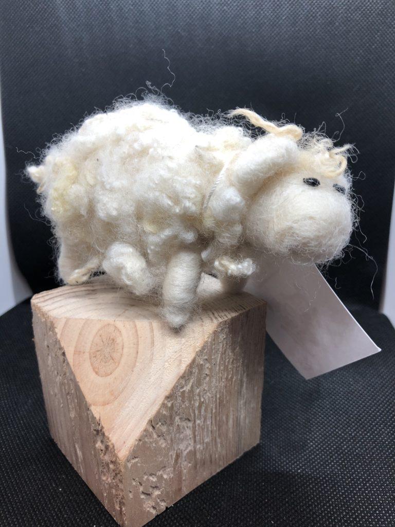 white felted sheep balanced on block on wood