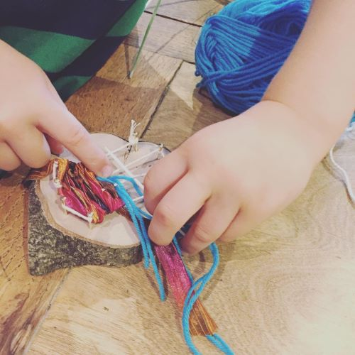 child's fingers weaving thread through string fastened to a piece of wood.