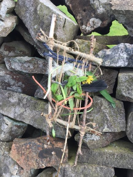 thread woven around stick framework and placed of dry stone wall