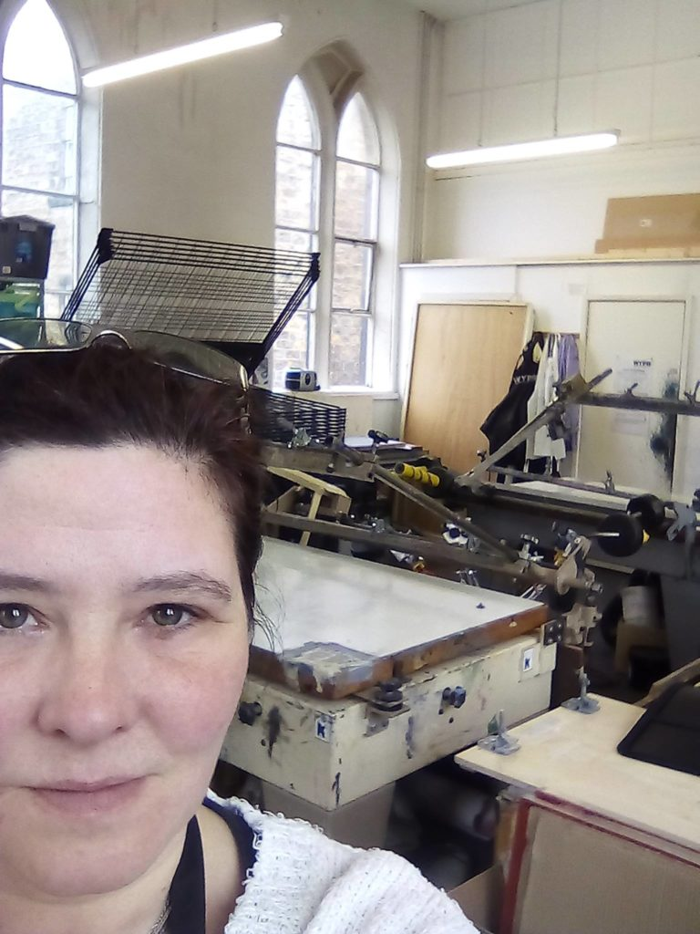 close up of white woman's face with dark hair and screenprinting studio and equipment in the background