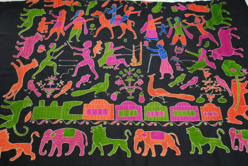 orange, blue, pink and green embroidered animals and people on a black cloth background