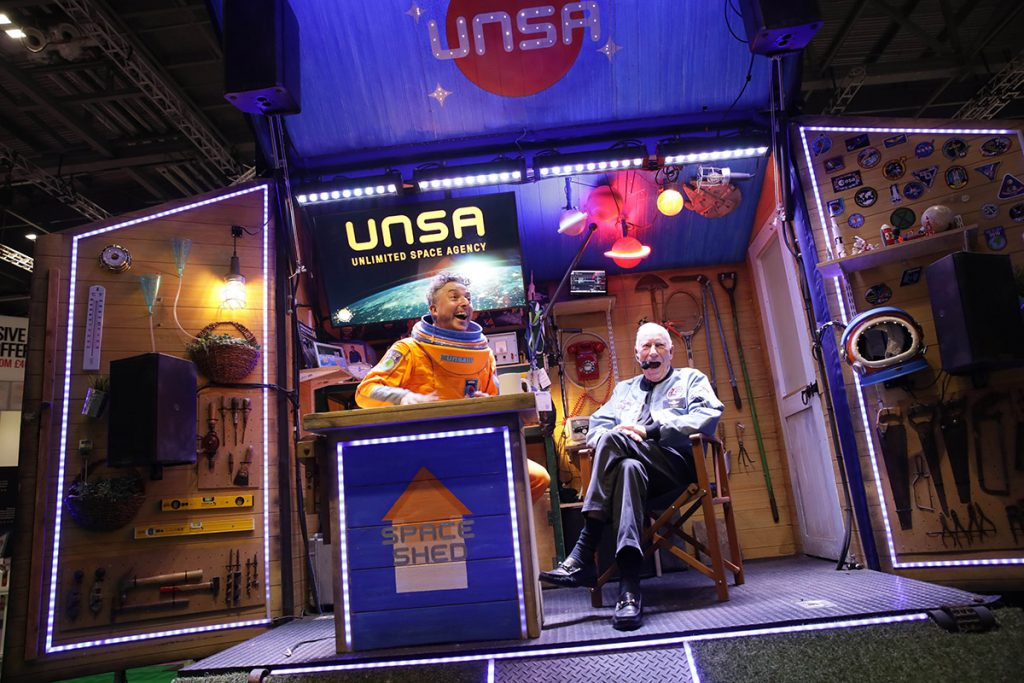 An open fronted shed with space themed lighting. A man wearing a spacesuit talking with an older man in jeans and a grey jacket