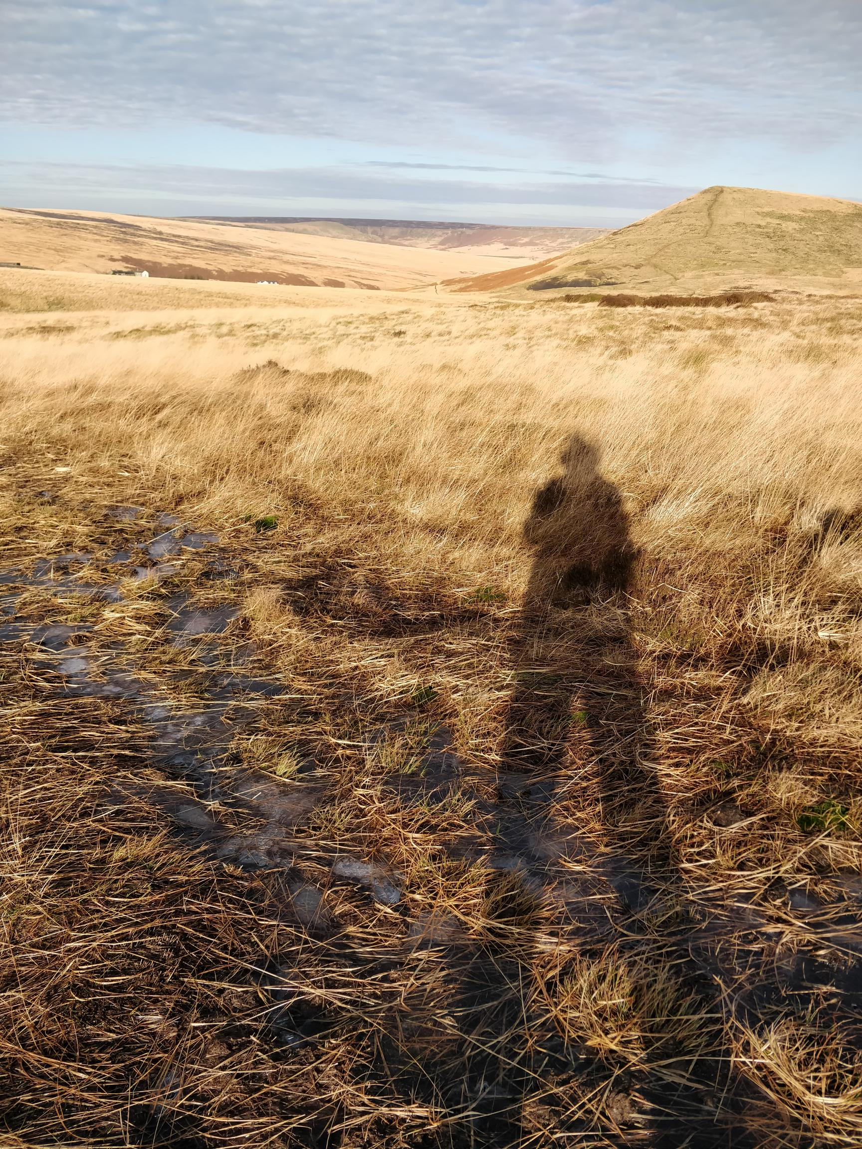 long shadow of a figure with sunny moorland and hills in the background